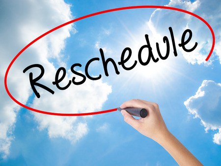 Woman Hand Writing Reschedule  with black marker on visual screen. Isolated on Sunny Sky. Business concept. Stock Photo Stock Photo