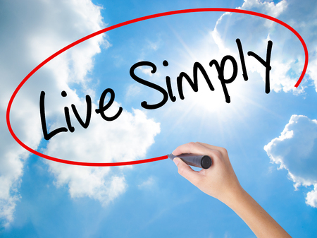 Woman Hand Writing Live Simply with black marker on visual screen. Isolated on Sunny Sky. Business concept. Stock Photo Stock Photo