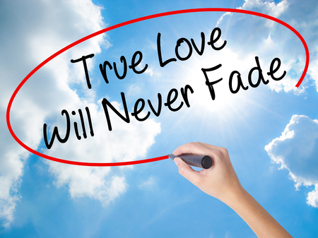 Woman Hand Writing True Love Will Never Fade with black marker on visual screen. Isolated on Sunny Sky. Business concept. Stock Photo