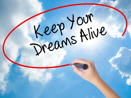 Woman Hand Writing Keep Your Dreams Alive with black marker on visual screen. Isolated on Sunny Sky. Business concept. Stock Photo Standard-Bild