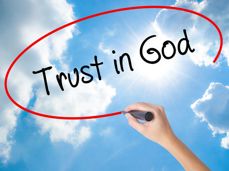 Woman Hand Writing Trust in God with black marker on visual screen. Isolated on Sunny Sky. Business concept. Stock Photo