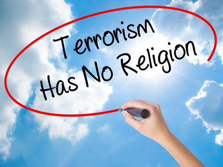 Woman Hand Writing Terrorism Has No Religion  with black marker on visual screen. Isolated on Sunny Sky. Business concept. Stock Photo