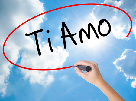Woman Hand Writing Ti Amo (I Love You In Italian) with black marker on visual screen. Isolated on Sunny Sky. Business, technology, internet concept. Stock  Photo Stock Photo