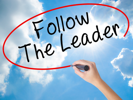 Woman Hand Writing Follow The Leader with black marker on visual screen. Isolated on Sunny Sky. Business concept. Stock Photo