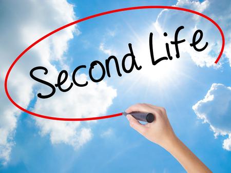 cronologia: Mano de la mujer que escribe Second Life con el marcador negro en la pantalla visual. Aislado en el cielo soleado. Concepto de negocio. Foto de stock Foto de archivo