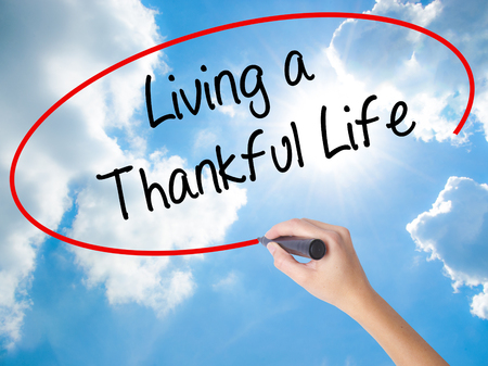 humility: Woman Hand Writing Living a Thankful Life with black marker on visual screen. Isolated on Sunny Sky. Business, technology, internet concept.