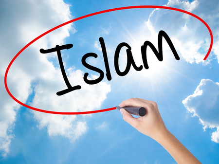 Woman Hand Writing Islam with black marker on visual screen. Isolated on Sunny Sky. Business concept. Stock Photo