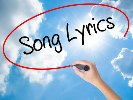 rhyme: Woman Hand Writing Song Lyrics with black marker on visual screen. Isolated on Sunny Sky. Business concept. Stock Photo Stock Photo