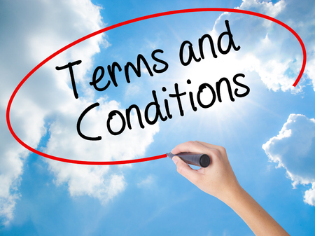 Woman Hand Writing Terms and Conditions with black marker on visual screen. Isolated on Sunny Sky. Business concept. Stock Photo