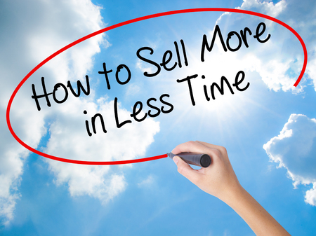 work less: Woman Hand Writing How to Sell More in Less Time with black marker on visual screen. Isolated on Sunny Sky. Business concept. Stock Photo Stock Photo