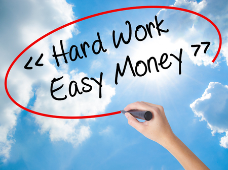 Woman Hand Writing Hard Work - Easy Money with black marker on visual screen. Isolated on Sunny Sky. Business concept. Stock Photo Stock Photo