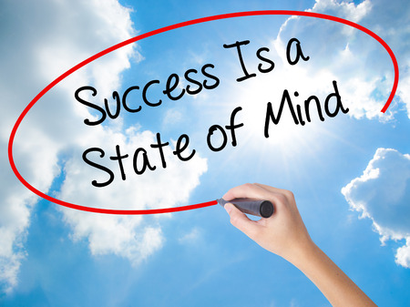 Woman Hand Writing Success Is a State of Mind with black marker on visual screen. Isolated on Sunny Sky. Business concept. Stock Photo