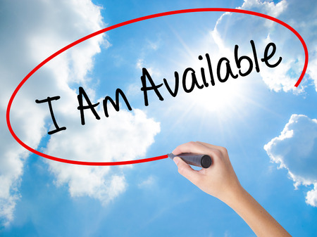 Woman Hand Writing I Am Available with black marker on visual screen. Isolated on Sunny Sky. Business concept. Stock Photo