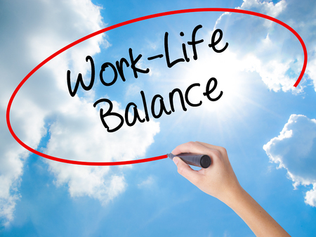 Woman Hand Writing Work-Life Balance with black marker on visual screen. Isolated on Sunny Sky. Business concept. Stock Photo Stock Photo