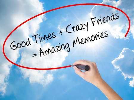 Woman Hand Writing Good Times + Crazy Friends = Amazing Memories with black marker on visual screen. Isolated on Sunny Sky. Business concept. Stock Photo