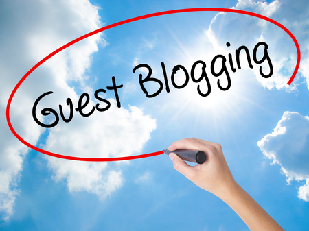 Woman Hand Writing Guest Blogging  with black marker on visual screen. Isolated on Sunny Sky. Business concept. Stock Photo