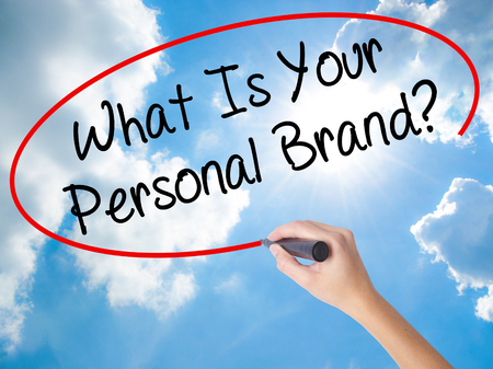 singularity: Woman Hand Writing What Is Your Personal Brand? with black marker on visual screen. Isolated on Sunny Sky. Business concept. Stock Photo