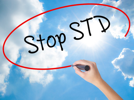 Woman Hand Writing Stop STD (Sexually transmitted diseases) with black marker on visual screen. Isolated on Sunny Sky. Business concept. Stock Photo