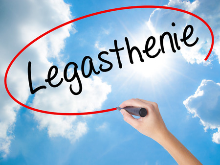 Woman Hand Writing Legasthenie (Dyslexia in German) with black marker on visual screen. Isolated on Sunny Sky. Business concept. Stock Photo