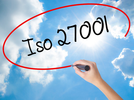 Woman Hand Writing Iso 27001  with black marker on visual screen. Isolated on Sunny Sky. Business concept. Stock Photo
