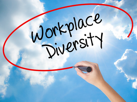 Woman Hand Writing Workplace Diversity  with black marker on visual screen. Isolated on Sunny Sky. Business concept. Stock Photo
