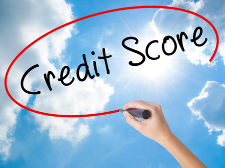 Woman Hand Writing Credit Score black marker on visual screen. Isolated on Sunny Sky. Business concept. Stock Photo