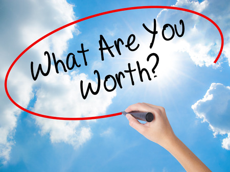 Woman Hand Writing What Are You Worth? with black marker on visual screen. Isolated on Sunny Sky. Business concept. Stock Photo Stock Photo