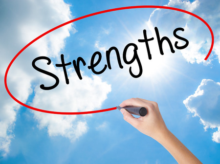 Woman Hand Writing Strengths with black marker on visual screen. Isolated on Sunny Sky. Business concept. Stock Photo