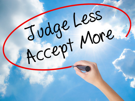 Woman Hand Writing Judge Less Accept More with black marker on visual screen. Isolated on Sunny Sky. Business concept. Stock Photo