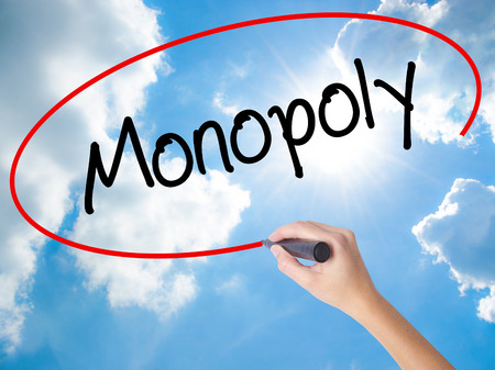 Woman Hand Writing Monopoly with black marker on visual screen. Isolated on Sunny Sky. Business concept. Stock Photo Stock Photo