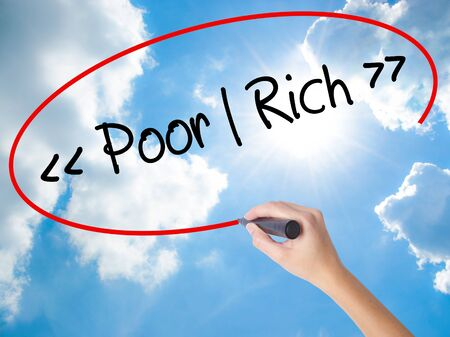 Woman Hand Writing Poor - Rich with black marker on visual screen. Isolated on Sunny Sky. Business concept. Stock Photo Stock Photo
