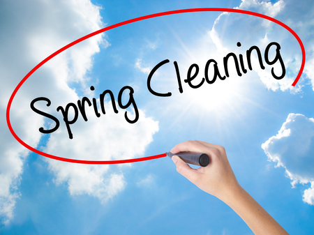 Woman Hand Writing Spring Cleaning with black marker on visual screen. Isolated on Sunny Sky. Business concept. Stock Photo