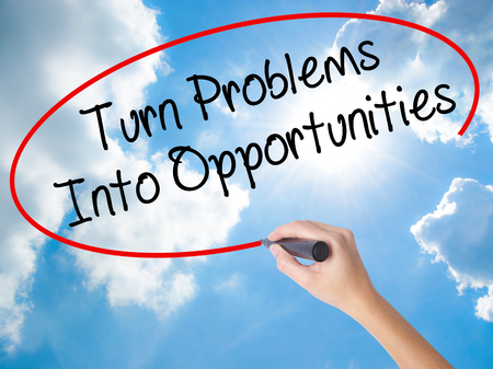 Woman Hand Writing Turn Problems into Opportunities with black marker on visual screen. Isolated on Sunny Sky. Business concept. Stock Photo Stock Photo