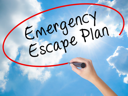 evacuacion: Woman Hand Writing Emergency Escape Plan with black marker on visual screen. Isolated on Sunny Sky. Business concept. Stock Photo