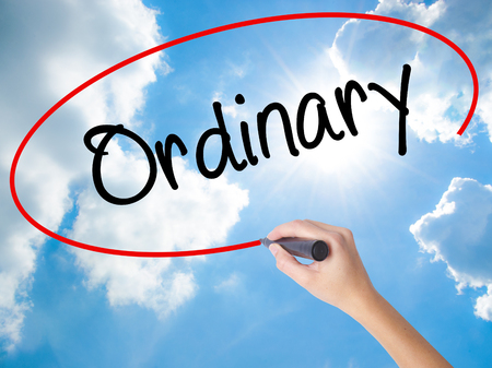 differentiation: Woman Hand Writing Ordinary with black marker on visual screen. Isolated on Sunny Sky. Business concept. Stock Photo