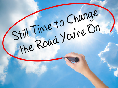 Woman Hand Writing Still Time to Change the Road Youre On with black marker on visual screen. Isolated on Sunny Sky. Business concept. Stock Photo