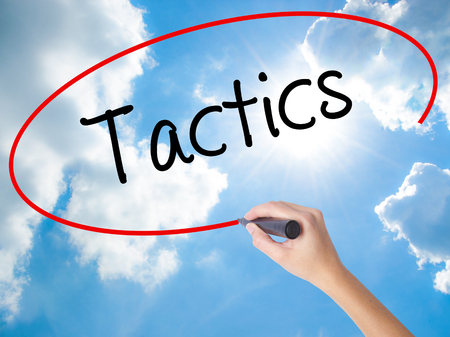 Woman Hand Writing Tactics with black marker on visual screen. Isolated on Sunny Sky. Business concept. Stock Photo