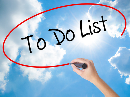 Woman Hand Writing To Do List with black marker on visual screen. Isolated on Sunny Sky. Business concept. Stock Photo