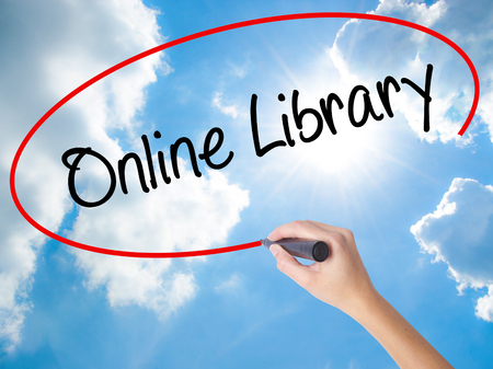 electronic book: Woman Hand Writing Online Library with black marker on visual screen. Isolated on Sunny Sky. Business, technology, internet concept. Stock Photo