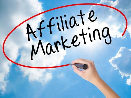 Woman Hand Writing Affiliate Marketing with black marker on visual screen. Isolated on Sunny Sky. Business concept. Stock Photo
