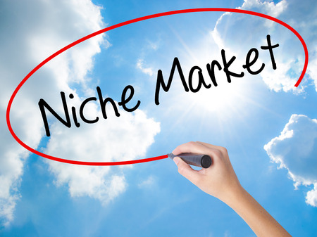 specific: Woman Hand Writing Niche Market with black marker on visual screen. Isolated on Sunny Sky. Business concept. Stock Photo