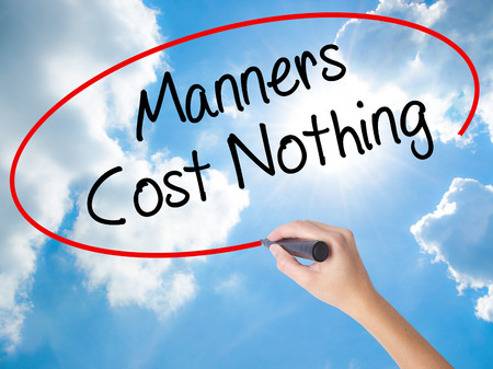 Woman Hand Writing Manners Cost Nothing with black marker on visual screen. Isolated on Sunny Sky. Business concept. Stock Photo Stock Photo