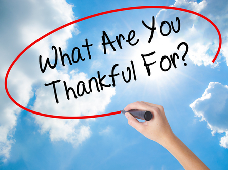 Woman Hand Writing What Are You Thankful For? with black marker on visual screen. Isolated on Sunny Sky. Business, technology, internet concept. Stock Photo