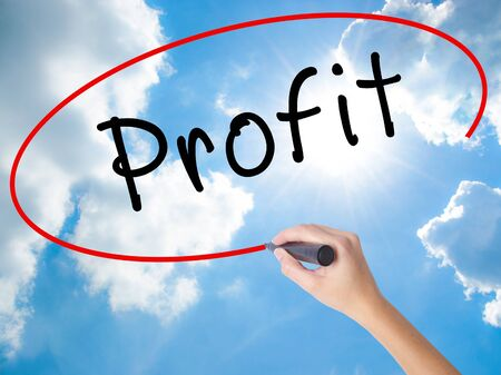Woman Hand Writing Profit with black marker on visual screen. Isolated on Sunny Sky. Business concept. Stock Photo Stock Photo