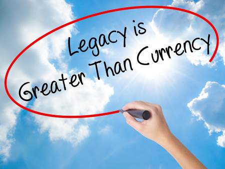 descendants: Woman Hand Writing Legacy is Greater Than Currency with black marker on visual screen. Isolated on Sunny Sky. Business concept. Stock Photo Stock Photo