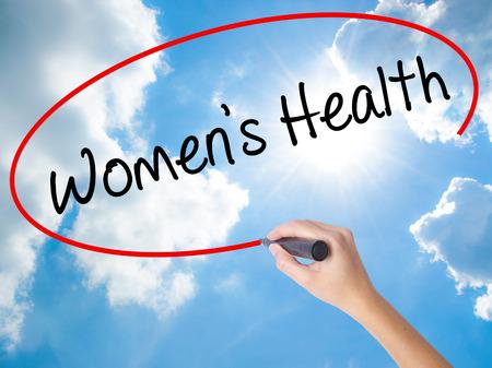 Femme main écrit la santé des femmes avec un marqueur noir sur l'écran visuel. Isolé sur ciel ensoleillé. Concept d'affaires Photo en stock