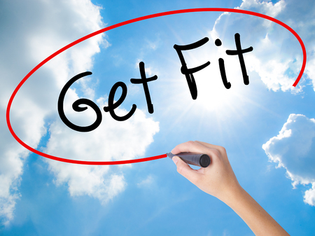 work less: Woman Hand Writing Get Fit  with black marker on visual screen. Isolated on Sunny Sky. Business concept. Stock Photo