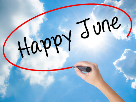 Woman Hand Writing Happy June with black marker on visual screen. Isolated on Sunny Sky. Business concept. Stock Photo