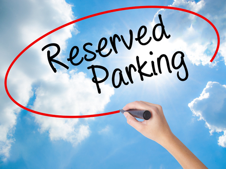 deficient: Woman Hand Writing Reserved Parking with black marker on visual screen. Isolated on Sunny Sky. Business concept. Stock Photo Stock Photo
