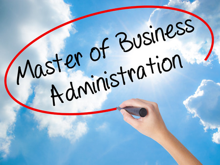 Woman Hand Writing Master of Business Administration with black marker on visual screen. Isolated on Sunny Sky. Business concept. Stock Photo